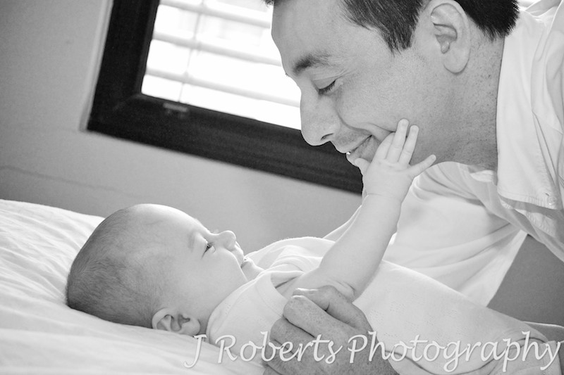 baby reaching up to touch dad's face - baby portrait photography sydney