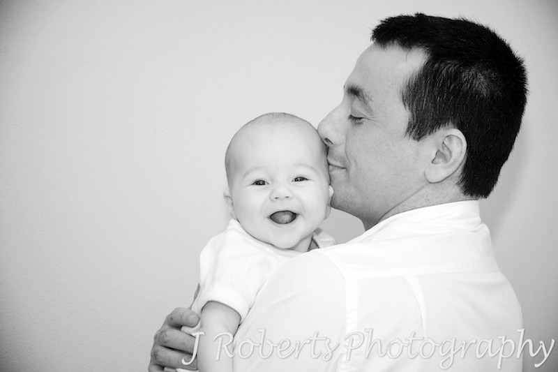 Baby laughing over Dad's shoulder - baby portrait photography sydney
