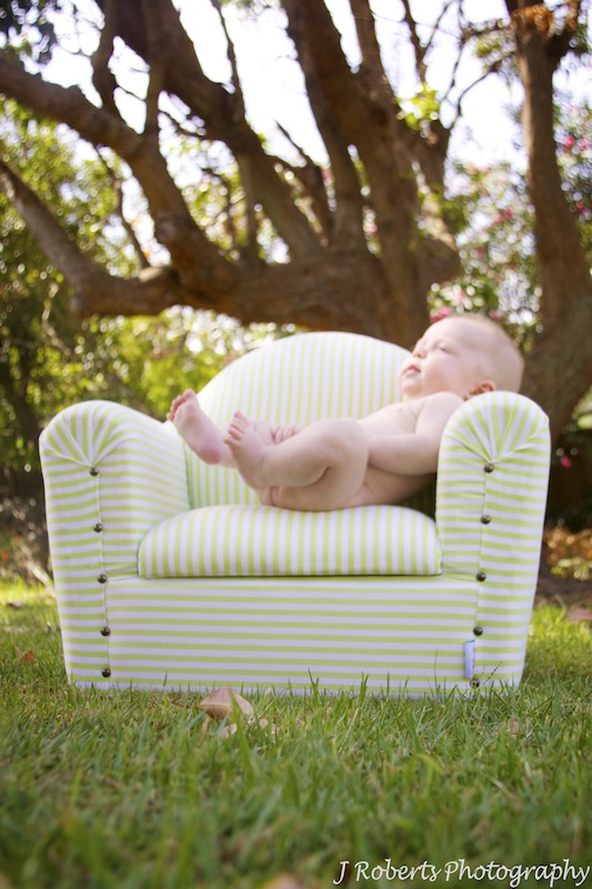 Baby lounging on couch in garden - baby portrait photography sydney