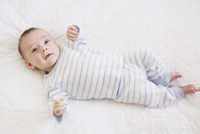 Baby lying on bed - baby portrait photography sydney
