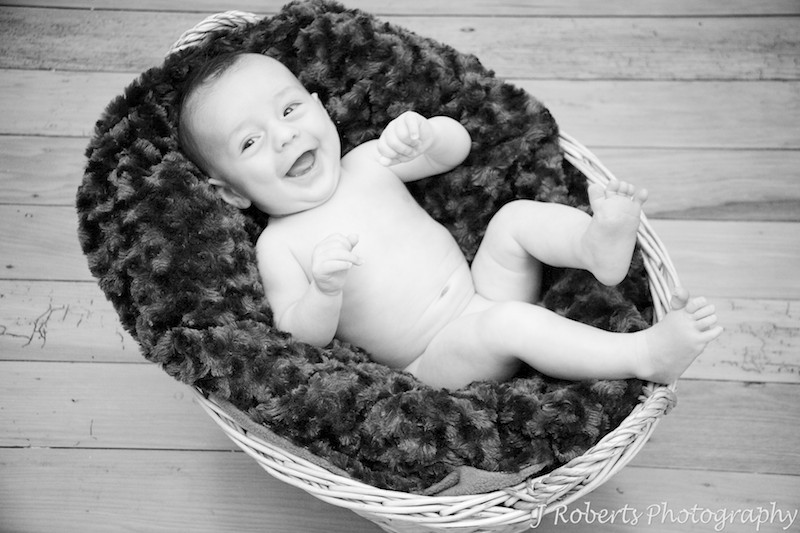 Laughing naked baby in basket - baby portrait photography sydney