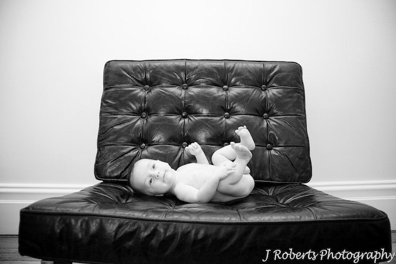 Naked baby boy on leather couch - baby portrait photography sydney