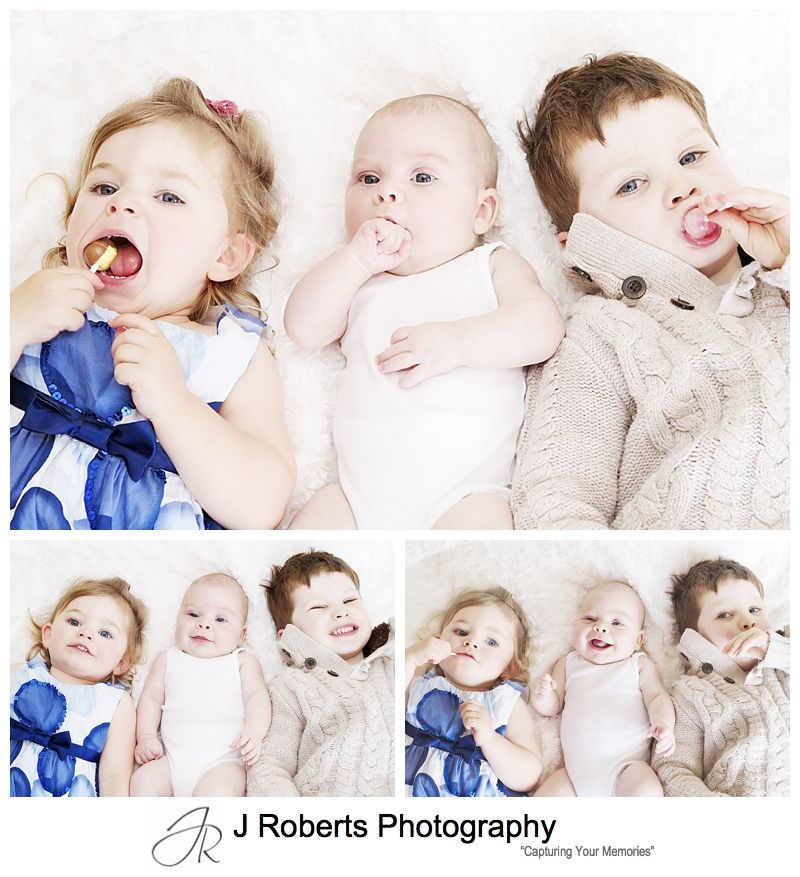 Baby boy with his big sister and brother licking lollipops - sydney baby portrait photography