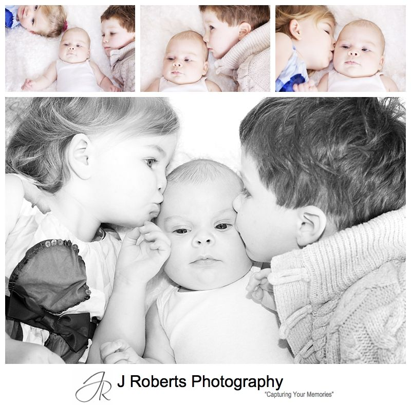 Baby boy being kissed by his older siblings - baby portrait photography sydney