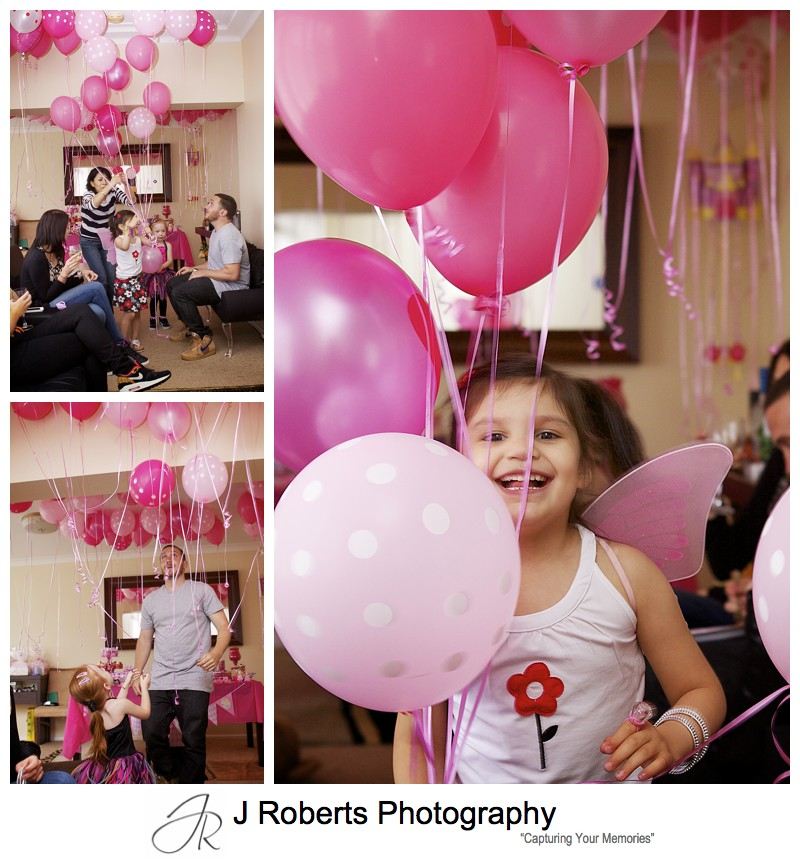 Little girls playing with lots of pink helium balloons at birthday party - sydney party photography