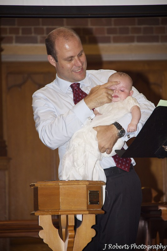 Sign of cross on baby boy being christened - christening photography sydney