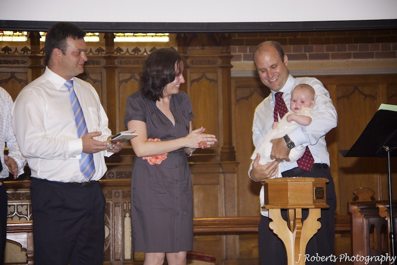 Parents watching baby being christened - christening photography