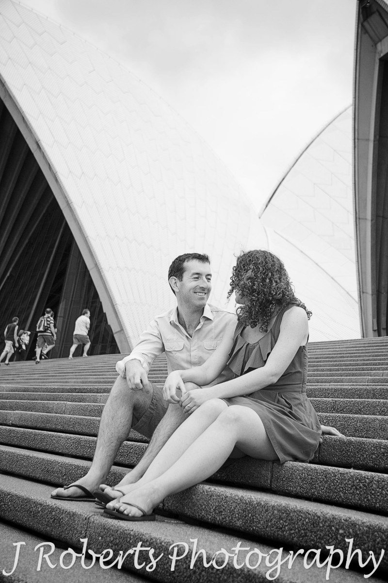 Engaged couple sitting on the Sydney Opera House steps - engagement photography sydney
