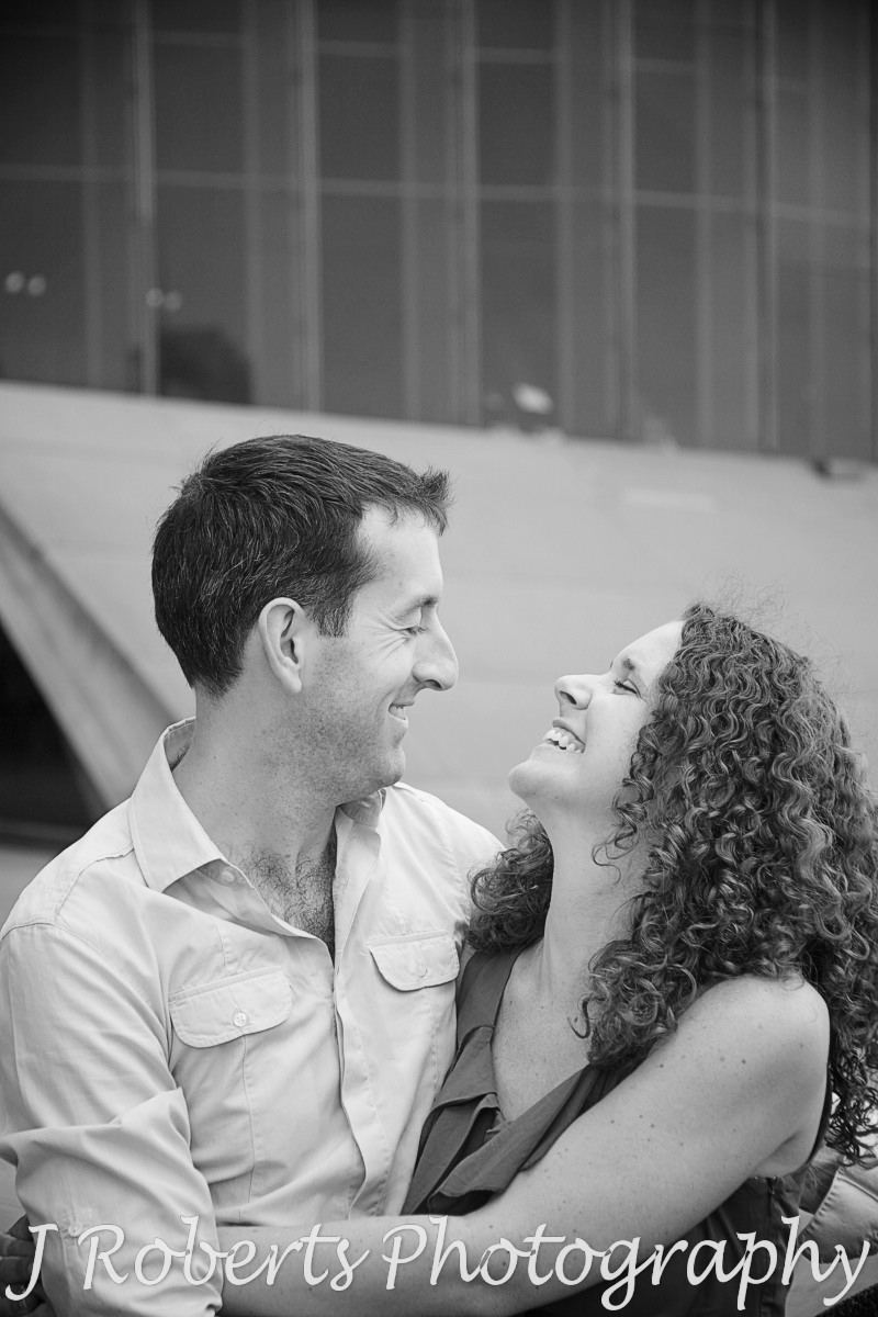 Couple laughing together on Sydney Opera House forecourt - engagement photography sydney
