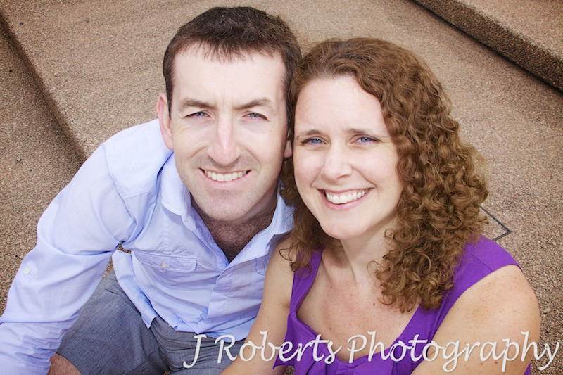 Engaged couple smiling up at the camera - engagement photography sydney