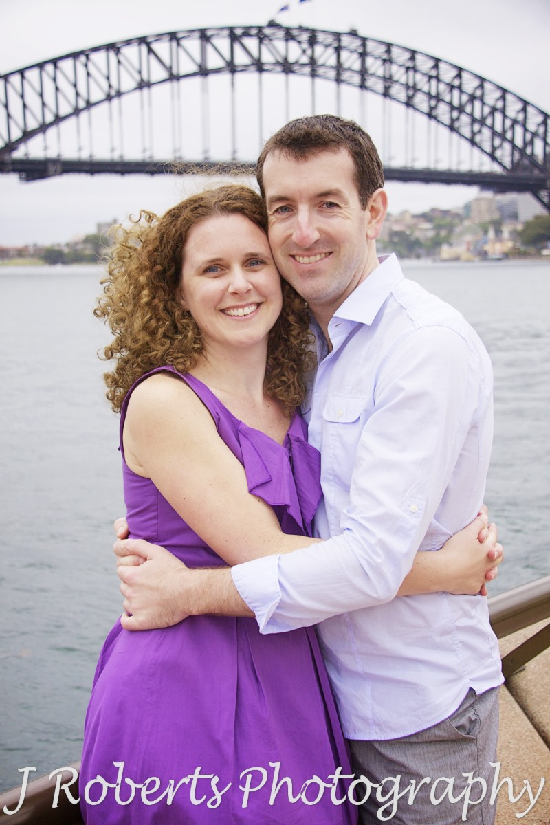 Portrait of a couple in front of Sydney Harbour Bridge - engagement photography sydney