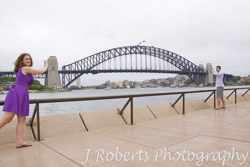 Couple pushing the pylons of Sydney Harbour Bridge together - engagement photography sydney