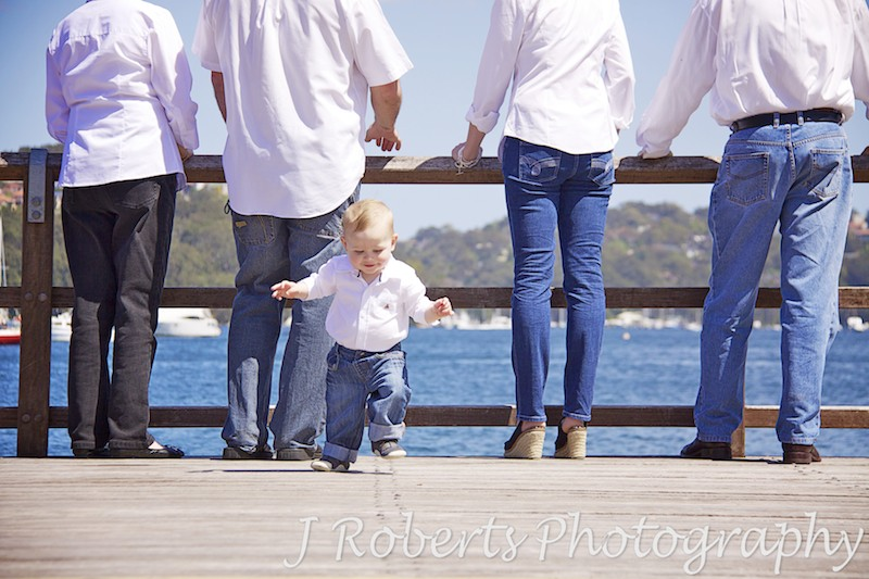 Little boy running away from parents & grandparents - family portrait photography sydney