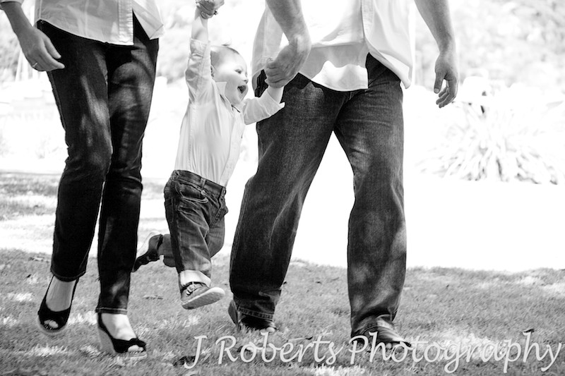 Little boy being swung by parents - family portrait photography sydney