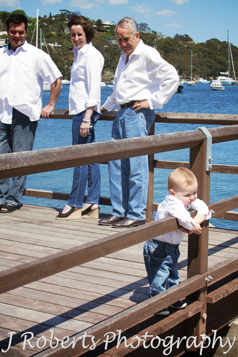 Little boy leaning over railing looking at water - family portrait photography sydney