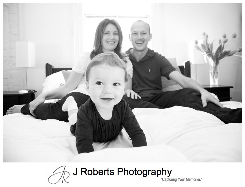 Baby girl with parents on her bed - family portrait photography sydney