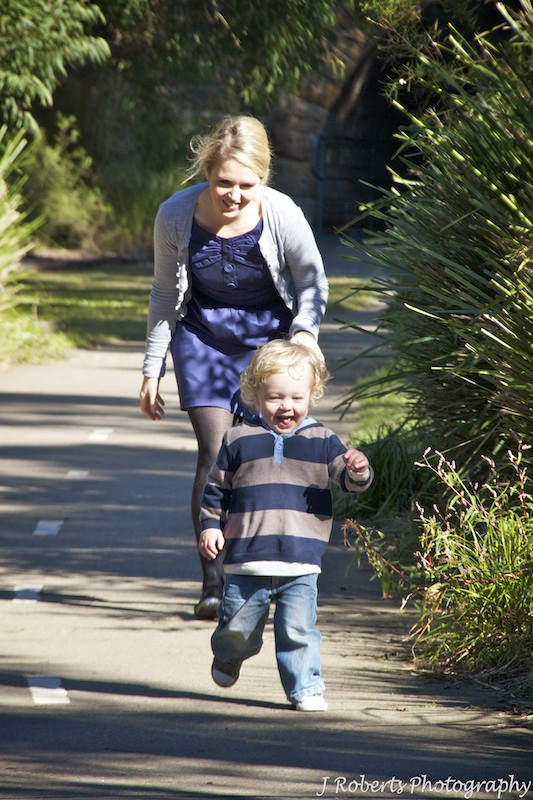 Mum chasing little giggling boy - family portrait photography sydney