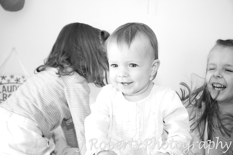 Little girl laughing as her sisters bounce her on the bed - family portrait photography sydney