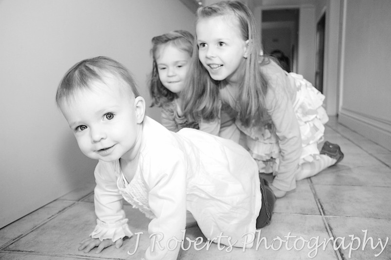 crawling race between 3 sisters - family portrait photography sydney