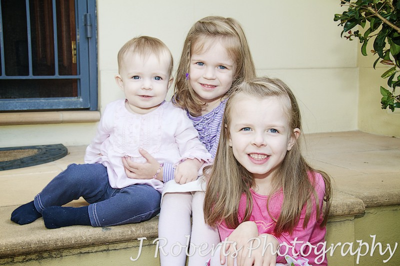 3 sisters sitting on steps - family portrait photography sydney