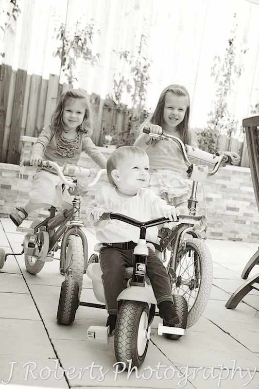 sisters riding bikes and tricycles - family portrait photography sydney