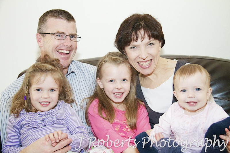 Family of 5 laughing on the couch - family portrait photography sydney