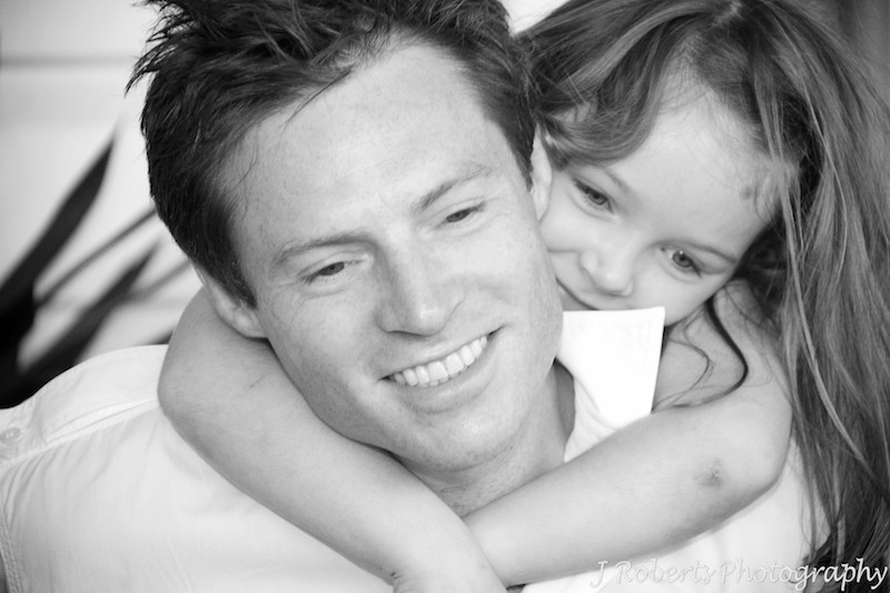 Daughter hugging father around the neck - family portrait photography sydney