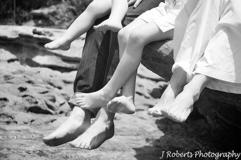 Family legs dangling from the rocks at the beach - family portrait photography sydney