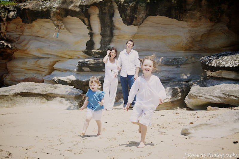 Kids having a running race on the beach - family portrait photography sydney