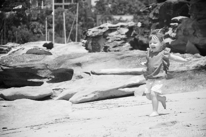 Little girl running with glee along the beach - family portrait photography sydney