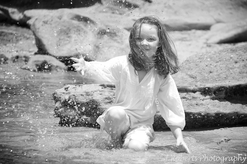 Little girl splashing water at fair light beach - family portrait photography sydney