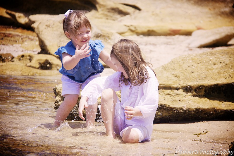Sisters splashing each other at the beach - family portrait photography sydney