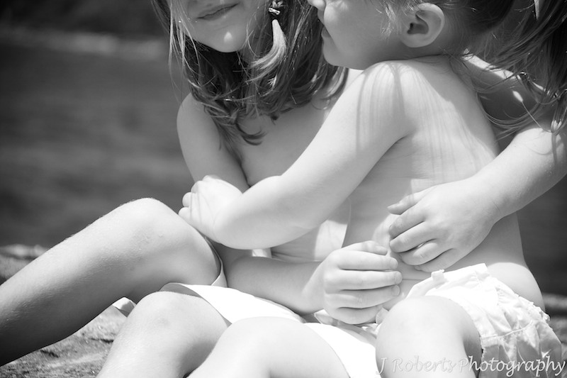 Sisters hugging arms at the beach - family portray photography sydney