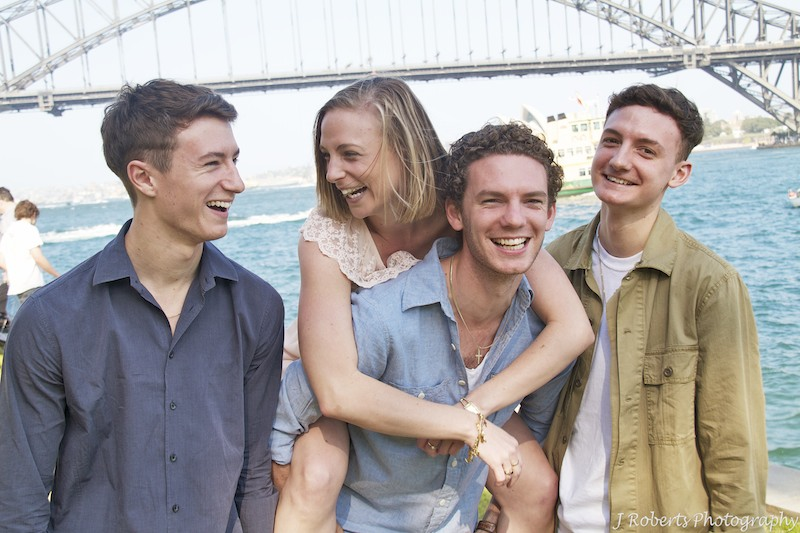 fun brothers and sisters piggyback shot in front of harbour bridge - Family Portrait Photography Sydney