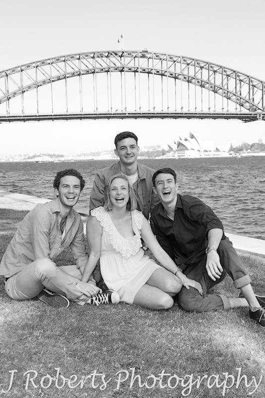 laughing siblings sitting on grass with harbour views in background - Family Portrait Photography Sydney
