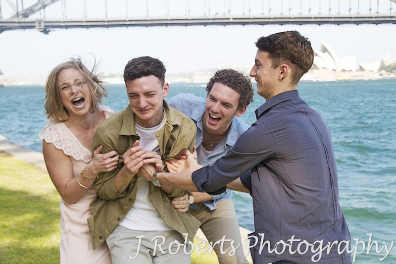 brothers and sisters tickling and having fun. Harbour views - Family Portrait Photography Sydney