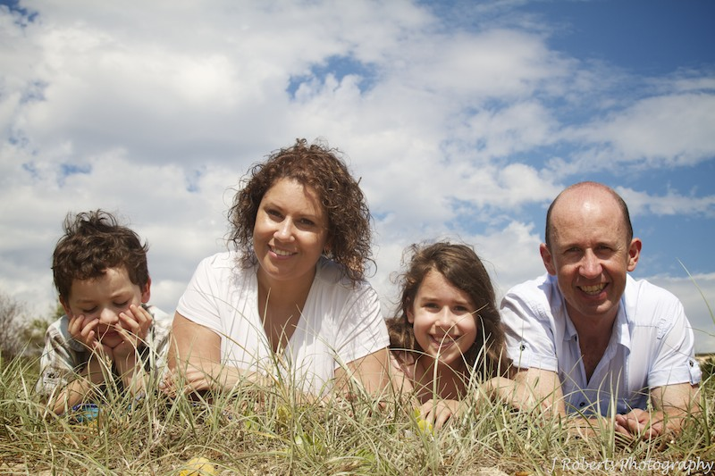 Family lying in the dunes at beach - family portrait photography