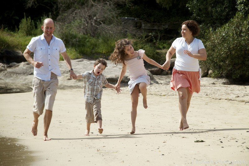 family running along beach - family portrait photography
