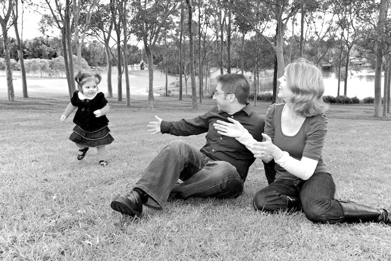 B&W little girl running away from parents open arms - family portrait photography sydney