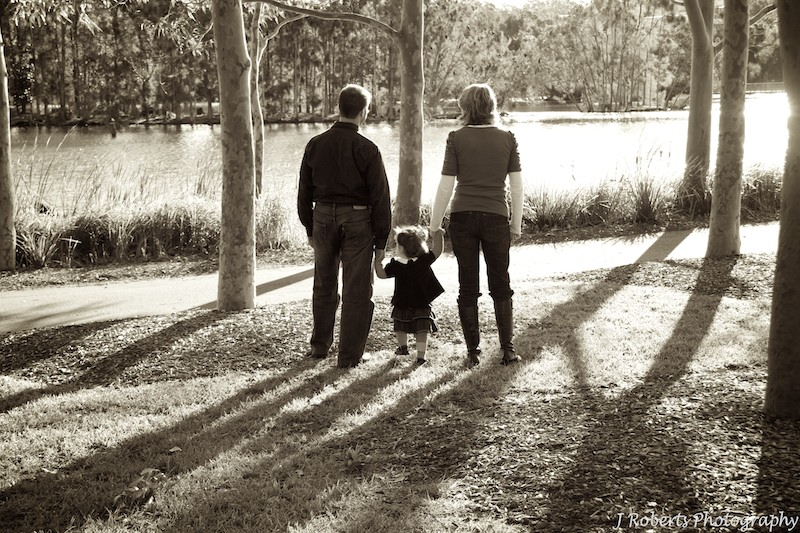 Sepia family of 3 walking hand in hand at the park - family portrait photography sydney