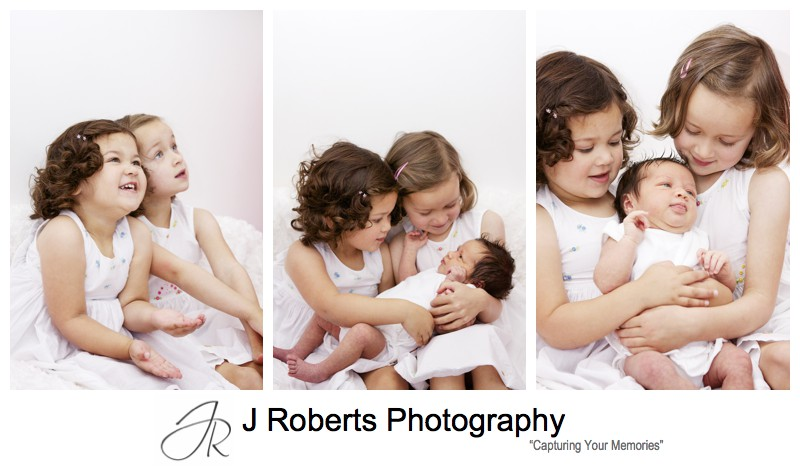 Older sisters holding their newborn baby sister - baby portrait photography sydney