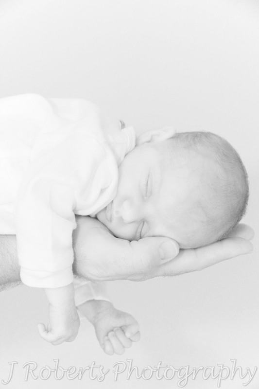 Baby sleeping in father's hand - newborn portrait photography sydney
