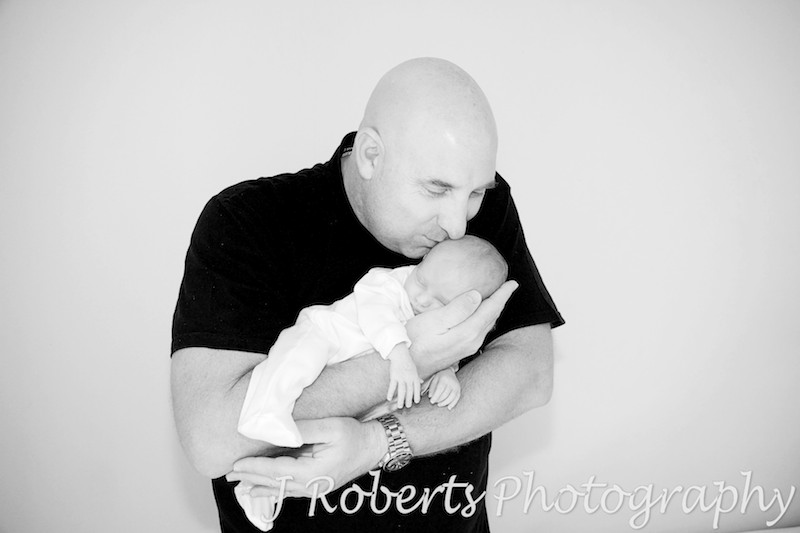 Daddy kissing sleep baby in his arms - baby portrait photography sydney