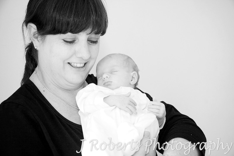 Mother smiling down at newborn baby in her arms - baby portrait photography sydney