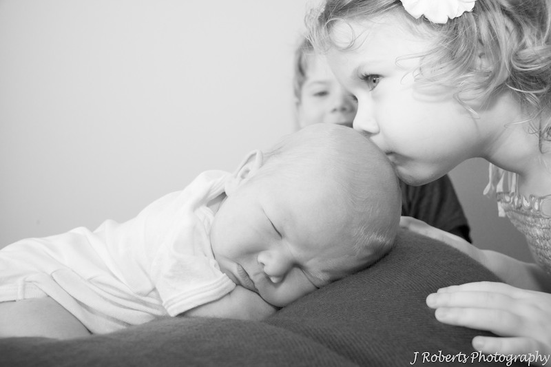Big sister kissing newborn baby - newborn portrait photography