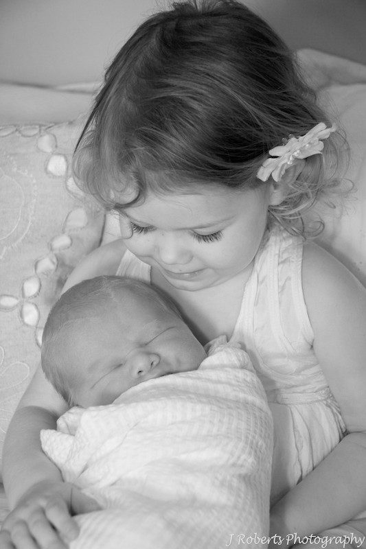 Big sister cuddling baby - newborn portrait photography