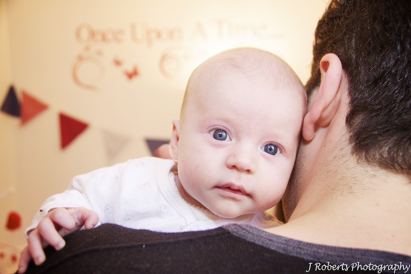 Baby looking over fathers shoulder - baby portrait photography sydney