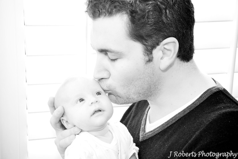 B&W of baby being kissed by father - baby portrait photography sydney