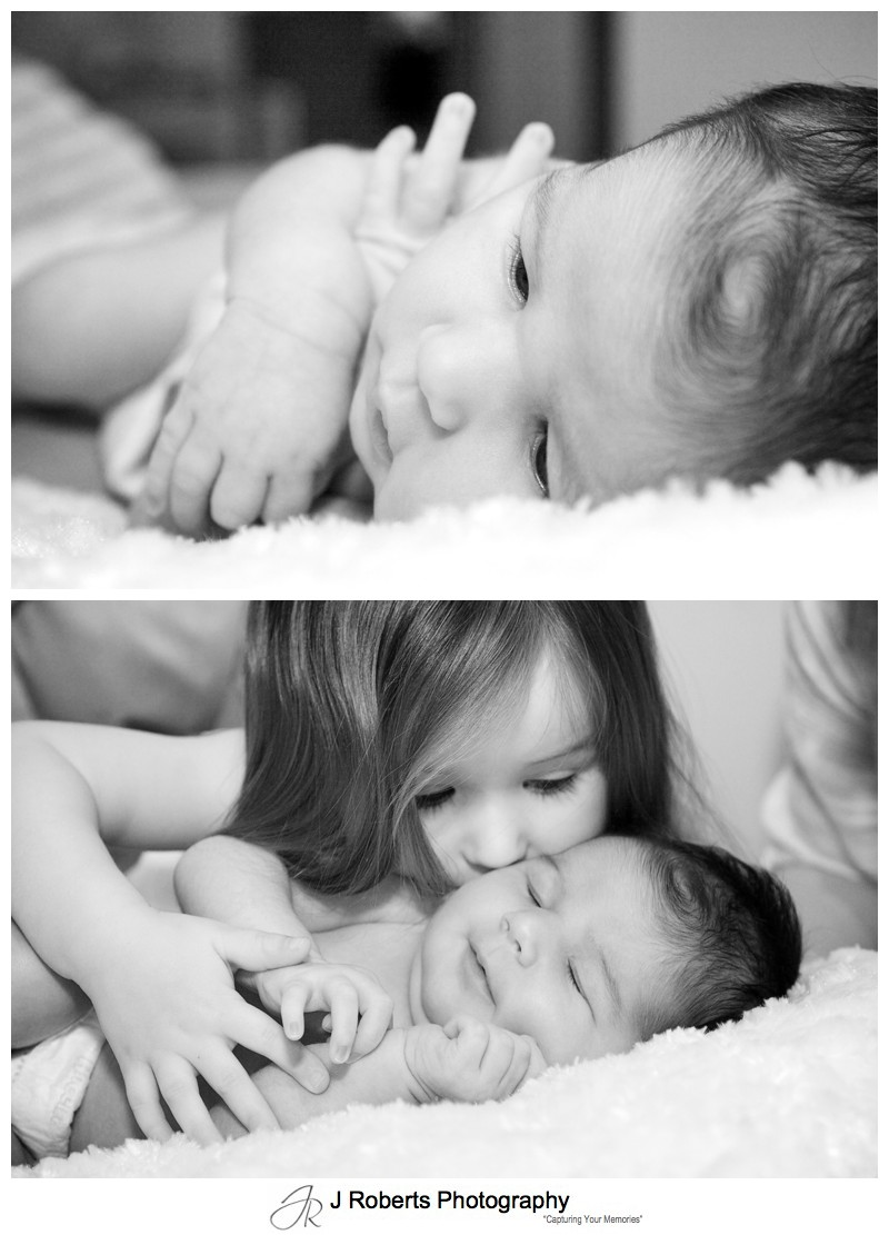 B&W portraits of newborn baby with her big sister kissing her - newborn portrait photography sydney