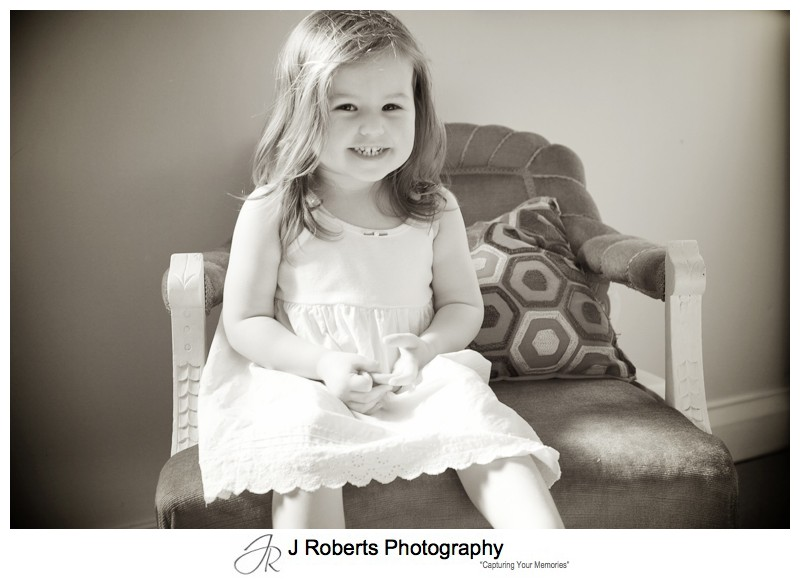Sepia portrait of 2 year old girl on old fashioned seat - family portrait photography sydney